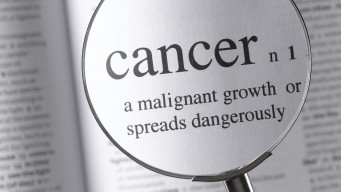 a magnifying glass magnifying the definition of cancer in a dictonary