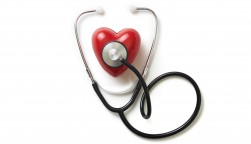 A stethoscope on a red plastic heart