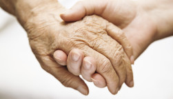 one hand holds the other elderly hand