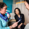 Deanna Saltzman (left) tests her lung function as Guang-Shing Cheng, MD (center), and Lisa Chung look on.