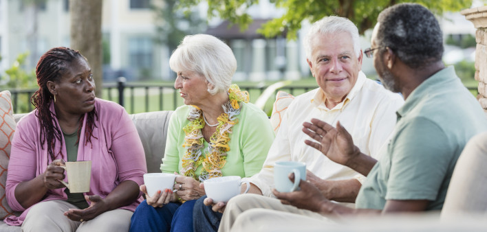 Two older couples hanging out on patio